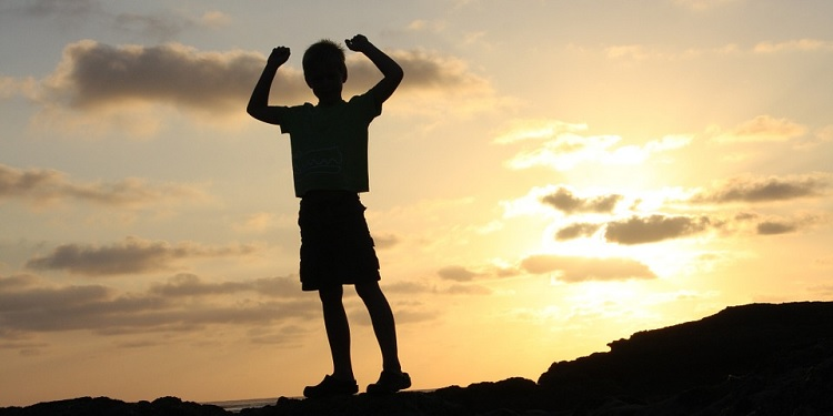 a young boy in shadow standing on a cliff with his arms raised in victory
