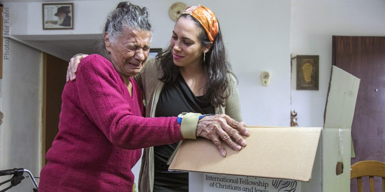 Yael Eckstein delivering a box of food & goods to elderly Holocaust survivor in need named Edna