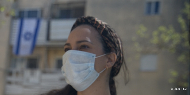 Yael Eckstein wears mask in new world of pandemic, with Israeli flag in background