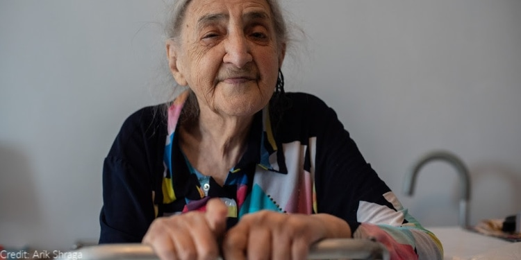 elderly woman, walker, eyes closed, black and multicolored patterned shirt
