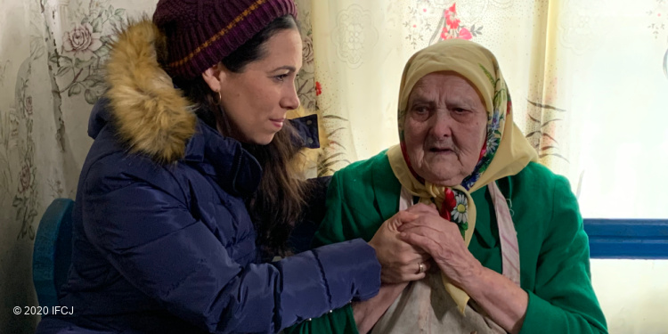 Yael Eckstein sits holding the hands of elderly woman wearing multiple layers of clothing