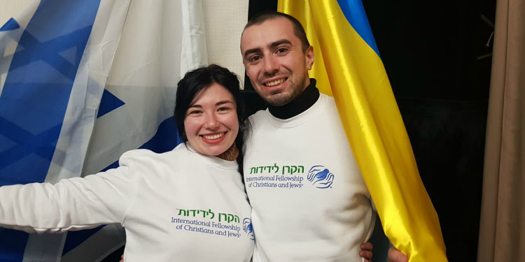Man and woman standing close to each other smiling. Surround by the Israeli flag.