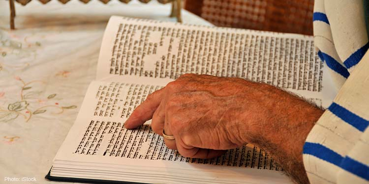 Close up of hand pointing to text in the Torah