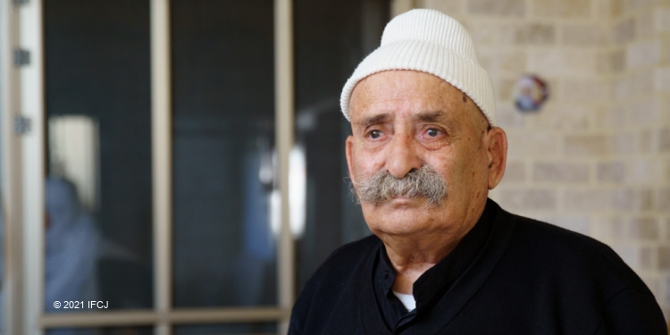 Winter Warmth package deliveries in Golan Heights, close up ofelderly man standing in courtyard, black shirt, white hat, moustache