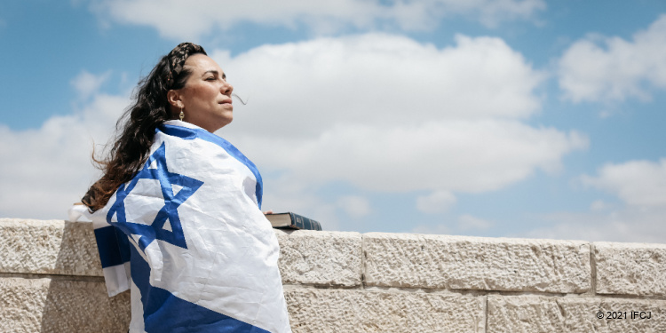 Yael stands near a low wall wrapped in flag of Israel, face turned up to the sun