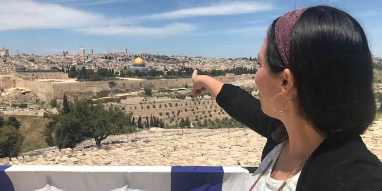 Yael Eckstein points at the Temple Mount in Jerusalem in the distance