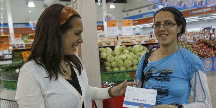 Yael Eckstein delivering a Passover food card to a young female recipient
