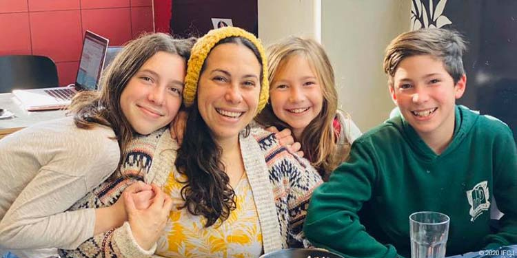 Yael Eckstein smiles while sharing a family hug with her kids