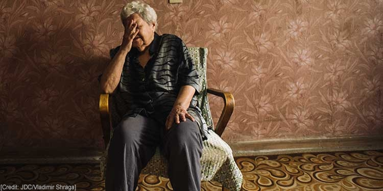 Elderly Jewish woman living in poverty sits in a chair with her hand over her face
