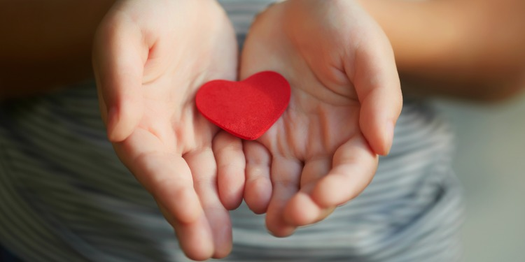 young girl holding red heart in open hands