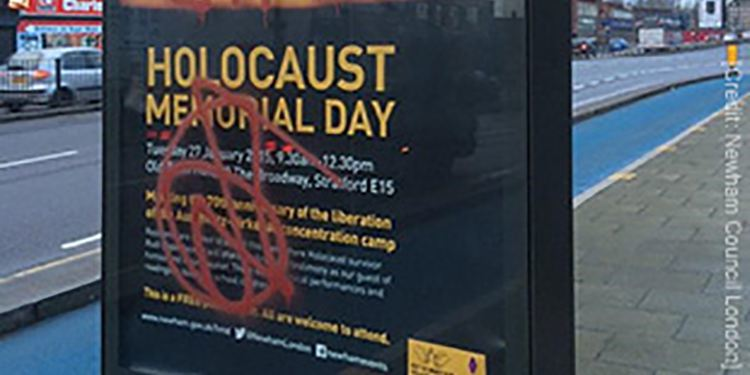 Graffiti stains a holocaust memorial poster