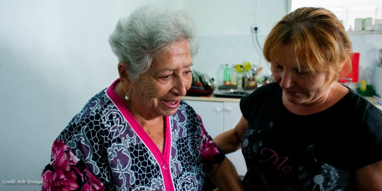 Elderly woman in Israel receiving assistance from a medical professional thanks to donations to IFCJ