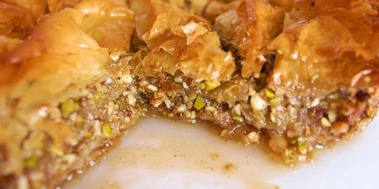 Delicious and flakey Baklava with a piece cut out of the side