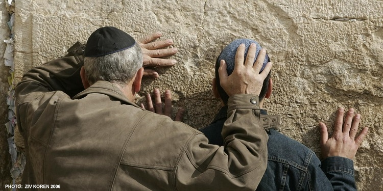 A man and young boy pray to the Western Wall in Jerusalem with their heads pressed against the wall
